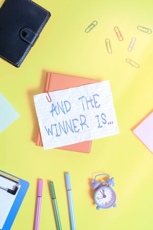 Writing note showing And The Winner Is. Business concept for announcing an individual or thing that wins something Flat lay above empty paper with pencils and paper clips