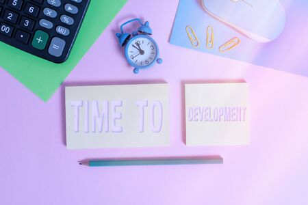 Handwriting text Time To Development. Conceptual photo a length of time during which a company grows or develop Wire mouse clock calculator notepads marker sheets clips color background Stock fotó
