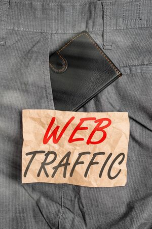 Word writing text Web Traffic. Business photo showcasing amount of web users and attempted visit measured of a website Small little wallet inside man trousers front pocket near notation paper
