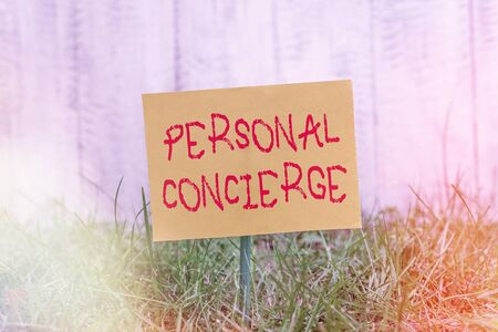 Writing note showing Personal Concierge. Business concept for someone who will make arrangements or run errands Plain paper attached to stick and placed in the grassy land