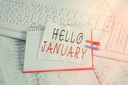 Handwriting text Hello January. Conceptual photo greeting used when welcoming the 1st month of the year notebook paper reminder clothespin pinned sheet white keyboard light wooden Stock Photo