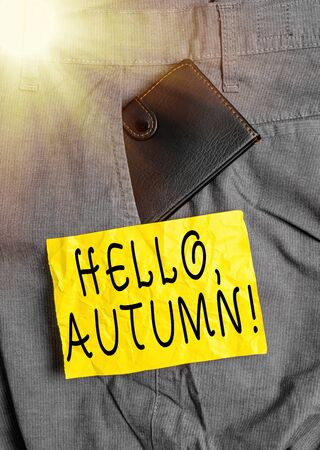 Word writing text Hello, Autumn. Business photo showcasing greeting used when embracing the change from summer to winter Small little wallet inside man trousers front pocket near notation paper