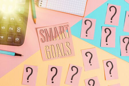 Text sign showing Smart Goals. Business photo showcasing mnemonic used as a basis for setting objectives and direction Mathematics stuff and writing equipment above pastel colours background