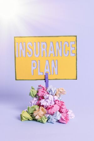 Text sign showing Insurance Plan. Business photo showcasing includes the risk management that a worker is covered Reminder pile colored crumpled paper clothespin reminder blue background