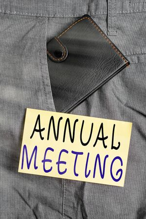 Writing note showing Annual Meeting. Business concept for scheduled annually for the discussion of the business future Small wallet inside trouser front pocket near notation paper