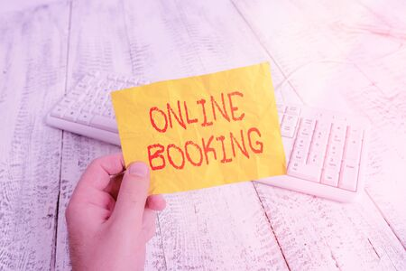 Text sign showing Online Booking. Business photo showcasing allows consumers to reserve for activity through the website man holding colorful reminder square shaped paper white keyboard wood floor
