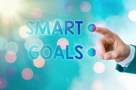 Writing note showing Smart Goals. Business concept for mnemonic used as a basis for setting objectives and direction