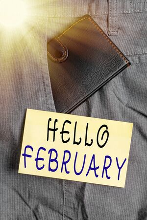 Writing note showing Hello February. Business concept for greeting used when welcoming the second month of the year Small wallet inside trouser front pocket near notation paper