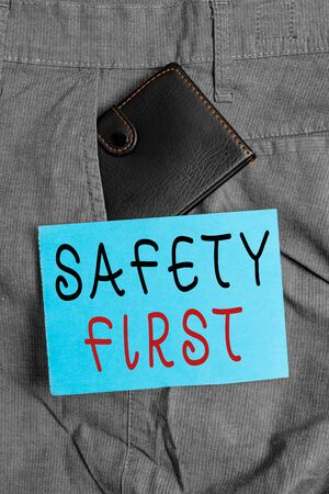 Handwriting text Safety First. Conceptual photo used to say that the most important thing is to be safe Small little wallet inside man trousers front pocket near notation paper