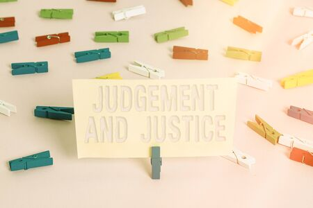 Conceptual hand writing showing Judgement And Justice. Concept meaning law court proceedings to present evidence and finalize decision Colored clothespin papers empty reminder pink floor office Stock fotó