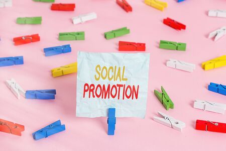 Writing note showing Social Promotion. Business concept for promoting a child to the next level regardless of skill Colored clothespin papers empty reminder pink floor office pin