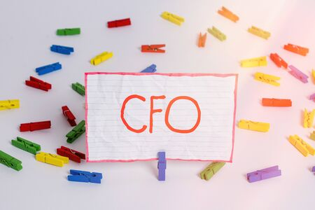 Conceptual hand writing showing Cfo. Concept meaning chief financial officer managing the financial actions of company Colored clothespin papers empty reminder white floor office Stock Photo