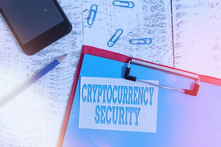 Handwriting text writing Cryptocurrency Security. Conceptual photo prevent unauthorized digital money transactions Clipboard paper sheet pencil note clips smartphone old wooden background