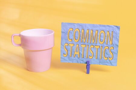 Handwriting text Common Statistics. Conceptual photo deals with collection analysis etc of numerical data Cup empty paper blue clothespin rectangle shaped reminder yellow office