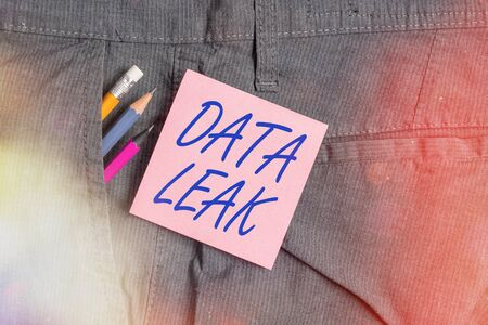 Conceptual hand writing showing Data Leak. Concept meaning released illegal transmission of data from a company externally Writing equipment and pink note paper inside pocket of trousers