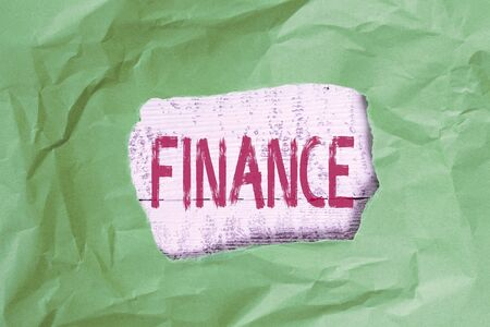 Conceptual hand writing showing Finance. Concept meaning describes activities associated with banking leverage or money Green crumpled colored paper sheet torn colorful background