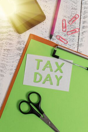 Text sign showing Tax Day. Business photo text due for individual income tax that should be submitted to the government Clipboard sheet pencil smartphone scissors note clips wooden background