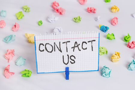 Word writing text Contact Us. Business photo showcasing contact information provided to assist customers needs Colored crumpled papers empty reminder white floor background clothespin