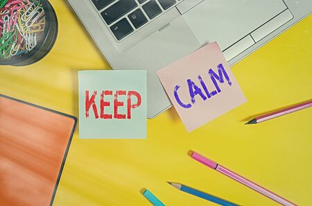 Writing note showing Keep Calm. Business concept for remain composure over situations with fewer emotions involved Laptop notes clips container notepad pencils markers colored background