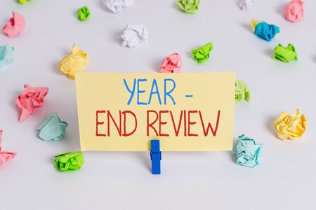 Conceptual hand writing showing Year end Review. Concept meaning annual assessment of achievement and goal development Colored crumpled paper empty reminder white floor clothespin