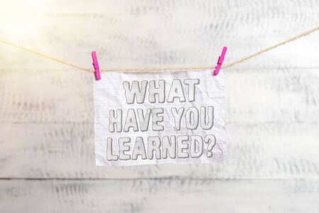 Handwriting text writing What Have You Learned Question. Conceptual photo to know the things acquire or absorb Clothesline clothespin rectangle shaped paper reminder white wood desk