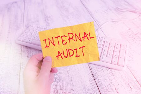 Text sign showing Internal Audit. Business photo showcasing evaluates the objective assurance to improve a firm s is operation man holding colorful reminder square shaped paper white keyboard wood floor