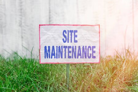 Text sign showing Site Maintenance. Business photo text Monitoring and regularly checking your website for issues Crumpled paper attached to a stick and placed in the green grassy land