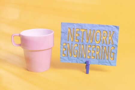 Handwriting text Network Engineering. Conceptual photo professional who has the skills to oversee the net Cup empty paper blue clothespin rectangle shaped reminder yellow office