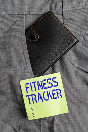 Writing note showing Fitness Tracker. Business concept for a monitoring device that records any healthrelated activity Small wallet inside trouser front pocket near notation paper Stock Photo