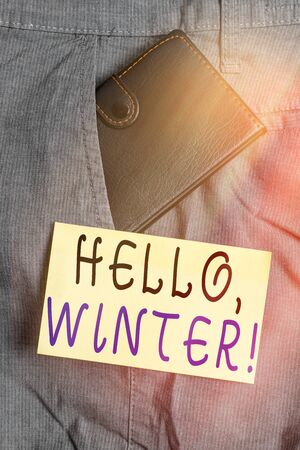 Writing note showing Hello, Winter. Business concept for greeting used when the cold season of the year passes by Small wallet inside trouser front pocket near notation paper