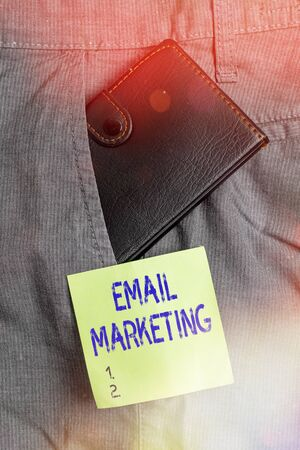 Writing note showing Email Marketing. Business concept for attracting potential buyer by communicating through the message Small wallet inside trouser front pocket near notation paper