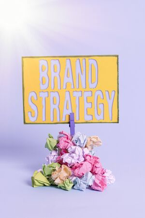 Text sign showing Brand Strategy. Business photo showcasing longterm plan executed for the development of a good product Reminder pile colored crumpled paper clothespin reminder blue background Stock Photo