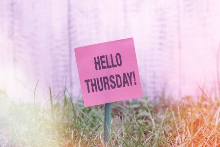 Writing note showing Hello Thursday. Business concept for a positive message as the Friday s is herald passes by Plain paper attached to stick and placed in the grassy land Stok Fotoğraf