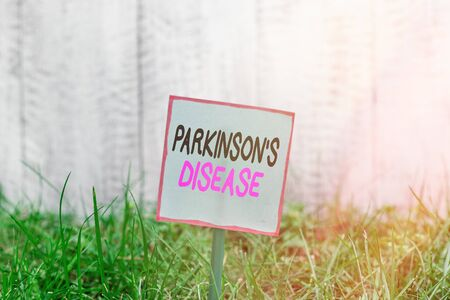 Word writing text Parkinsons Disease. Business photo showcasing chronic progressive neurological disease of later life Plain empty paper attached to a stick and placed in the green grassy land