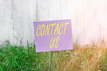 Writing note showing Contact Us. Business concept for contact information provided to assist customers needs Plain paper attached to stick and placed in the grassy land Banque d'images