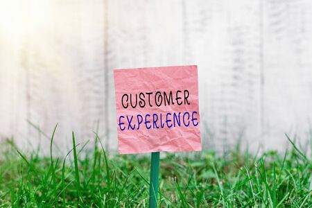 Conceptual hand writing showing Customer Experience. Concept meaning phrase to describe relationship user has with business Plain paper attached to stick and placed in the grassy land