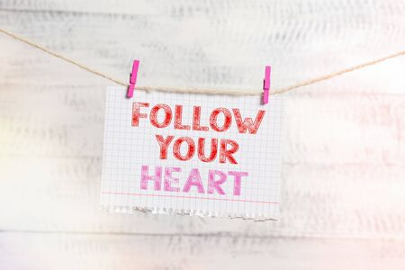 Writing note showing Follow Your Heart. Business concept for Motivation to do what is right and fulfill your desire Clothesline clothespin rectangle shaped paper reminder white wood desk