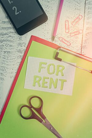 Text sign showing For Rent. Business photo text Occupying an establishment currently on a lease paid periodically Clipboard sheet pencil smartphone scissors note clips wooden background