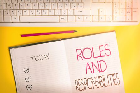 Writing note showing Roles And Responsibilities. Business concept for Business functions and professional duties Copy space on notebook above yellow background with keyboard on table