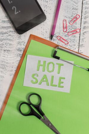 Text sign showing Hot Sale. Business photo text a very good discount of items is displayed over a limited time Clipboard sheet pencil smartphone scissors note clips wooden background