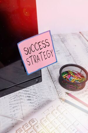Handwriting text Success Strategy. Conceptual photo provides guidance the bosses needs to run the company Note paper taped to black computer screen near keyboard and stationary