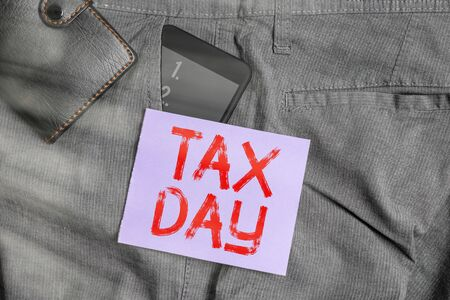 Writing note showing Tax Day. Business concept for due for individual income tax that should be submitted to the government Smartphone device inside trousers front pocket with wallet