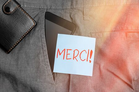 Conceptual hand writing showing Merci. Concept meaning thank you in French what is said when someone helps you in France Smartphone device inside trousers front pocket with wallet