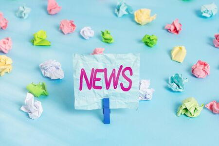 Handwriting text News. Conceptual photo comprehensive uptodate information from sources all over the world Colored crumpled papers empty reminder blue floor background clothespin