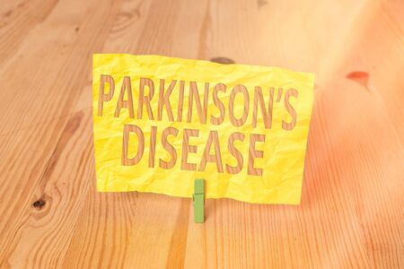 Conceptual hand writing showing Parkinsons Disease. Concept meaning chronic progressive neurological disease of later life Wooden floor background green clothespin groove slot office
