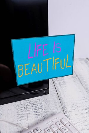 Word writing text Life Is Beautiful. Business photo showcasing Go to adventure vacation, enjoy and relax to satisfy nature every moment Notation paper taped to black computer monitor screen near white keyboard