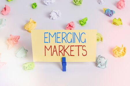 Conceptual hand writing showing Emerging Markets. Concept meaning nations that are investing in more productive capacity Colored crumpled paper empty reminder white floor clothespin