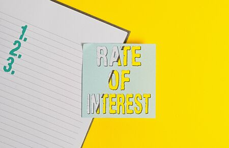 Conceptual hand writing showing Rate Of Interest. Concept meaning Percentage computed from principal amount of loan, mortgage, or investment Paper with copy space on yellow table. Paper for text messages Archivio Fotografico