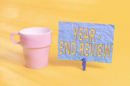 Handwriting text Year end Review. Conceptual photo annual assessment of achievement and goal development Cup empty paper blue clothespin rectangle shaped reminder yellow office 스톡 콘텐츠