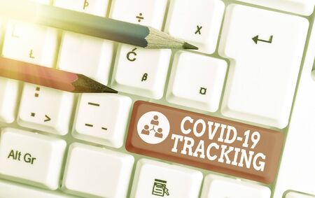 Text sign showing Covid 19 Tracking. Business photo showcasing Distinguishing process of the possible infected individuals White pc keyboard with empty note paper above white key copy space